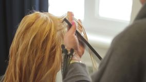 The hairdresser shears a woman with long blond hair. Haircut closeup stock video