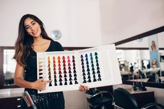Hairdresser showing hair color shade card at salon Stock Image