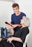 Hairdresser Showing Hair Product To Client Stock Photography