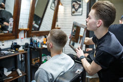 Hairdresser shows short haircut with mirror to handsome satisfied client in professional hairdressing salon royalty free stock photo