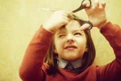 Hairdresser shutting eye from fear while cutting hair. Hairdresser, small, little child shutting eye from fear while cutting long, brunette, hair with metallic stock image