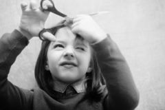 Hairdresser shutting eye from fear while cutting hair. Hairdresser, small, little child shutting eye from fear while cutting long, brunette, hair with metallic royalty free stock images