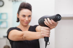 Hairdresser smiling and holding hairdryer Royalty Free Stock Photo
