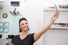 Hairdresser smiling and holding phone Royalty Free Stock Image