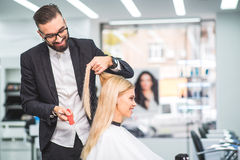 Hairdresser is smiling while working. Man is holding hair of a women and cutting it. Woman is smiling while sitting in chair Royalty Free Stock Photography