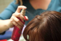 Hairdresser spray hair Royalty Free Stock Photography