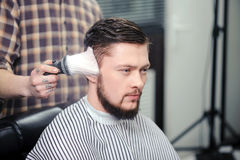 Hairdresser sprinkles a client with brush Royalty Free Stock Photos