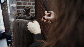The hairdresser sticks the artificial hair to the real thing. The process of hair extension. 4K
