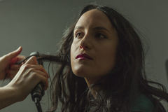 Hairdresser straighten womans hair in a set Stock Photos