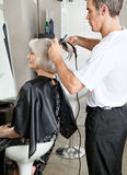 Hairdresser Straightening Female Client's Hair Royalty Free Stock Photo