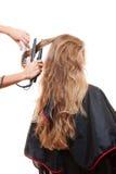 Hairdresser straightening hair Stock Photos