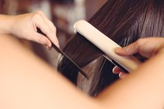 Hairdresser is straightening hair. At the hair salon royalty free stock image