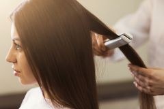 Hairdresser straightening long brown hair. With hair iron in professional beauty salon, side view stock photography