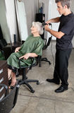 Hairdresser Straightening Senior Woman's Hair Stock Image