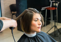 Hairdresser straightens hair of pretty woman Royalty Free Stock Photography