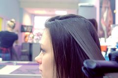Hairdresser straights dark brown hair of beautiful woman using hair tongs in beauty salon. Side view. Hairdresser straights dark brown hair of beautiful woman stock photography