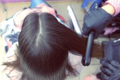 Hairdresser straights dark brown hair of beautiful woman using hair tongs in beauty salon. Back view. Hairdresser straights dark brown hair of beautiful woman stock photography