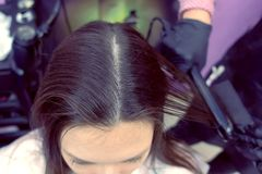 Hairdresser straights dark brown hair of beautiful woman using hair tongs in beauty salon. Top view. Hairdresser straights dark brown hair of beautiful woman royalty free stock images