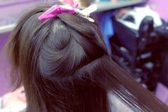 Hairdresser straights dark brown hair of woman using hair tongs in beauty salon. Hair close-up. Hairdresser straights brown hair of beautiful woman using hair royalty free stock photos
