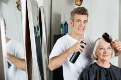Hairdresser Styling Client's Hair At Salon Stock Image