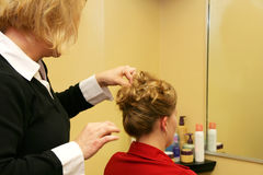 Hairdresser styling hair. Attractive young Caucasian blonde woman having hair styled for special event Stock Photos