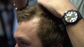 Hairdresser styling hair to a man stock video footage