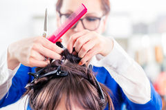 Hairdresser styling woman hair in shop royalty free stock photography