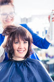 Hairdresser styling woman hair in shop stock images