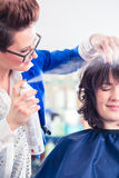 Hairdresser styling woman hair in shop royalty free stock images