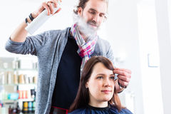 Hairdresser styling woman hair in shop Royalty Free Stock Image
