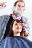 Hairdresser styling woman hair in shop royalty free stock photos