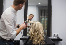 Hairdresser styling woman's hair Royalty Free Stock Photography