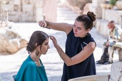 Hairdresser stylist makes a hairstyle for the model before shooting before shooting at Mt. Scopus in Jerusalem in Israel. Jerusalem, Israel, September 16, 2017 Royalty Free Stock Photo