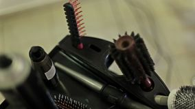 The hairdresser takes a hair spray from a table with combs, curling iron and other items for hair cutting and styling