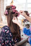 Hairdresser taking off curlers from woman long hair Royalty Free Stock Photo