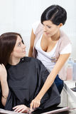 Hairdresser talking to the client sitting on chair Stock Images