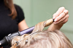 Hairdresser to curl the hair in a beauty salon Stock Images