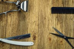 Hairdresser`s tools at the edges. Hairdresser tools on an old wooden background center Stock Photography