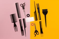 Hairdresser tools on pink and yellow background with copy space, top view, flat lay.