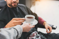Hairdresser treating her customer with hot beverage stock image