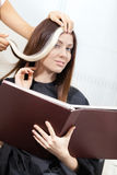 Hairdresser tries lock of dyed hair on the client Royalty Free Stock Photos