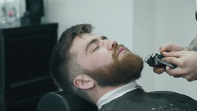 Hairdresser trimming beard with electric razor stock video footage