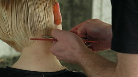 Hairdresser trimming blond hair with scissors. Professional shot on BMCC RAW with high dynamic range. You can use it e.g in your commercial video, hair salon stock video footage