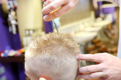 Hairdresser trimming blonde hair of young boy Stock Photo