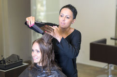 Hairdresser trimming the hair of a young woman Stock Image