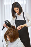 Hairdresser using a blow dryer. Hair salon employee and customer Stock Images