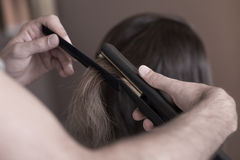 Hairdresser using a hair straightener Royalty Free Stock Photography