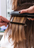 Hairdresser using a hair straightener. On the long brown hair of a female client, close up view of her hands Royalty Free Stock Images