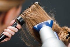 Hairdresser using hairbrush and hair-dryer royalty free stock image