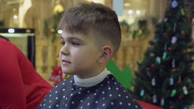 Hairdresser using hairdryer in barber`s. Boy six years old in barbershop. Happy little boy in beauty salon. Barber dries hair in hairdressing salon. Smiling kid stock video footage
